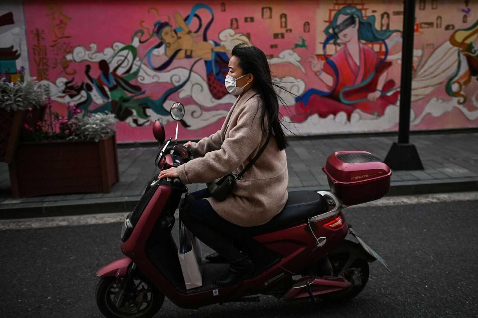 Una mujer con mascarilla monta en moto