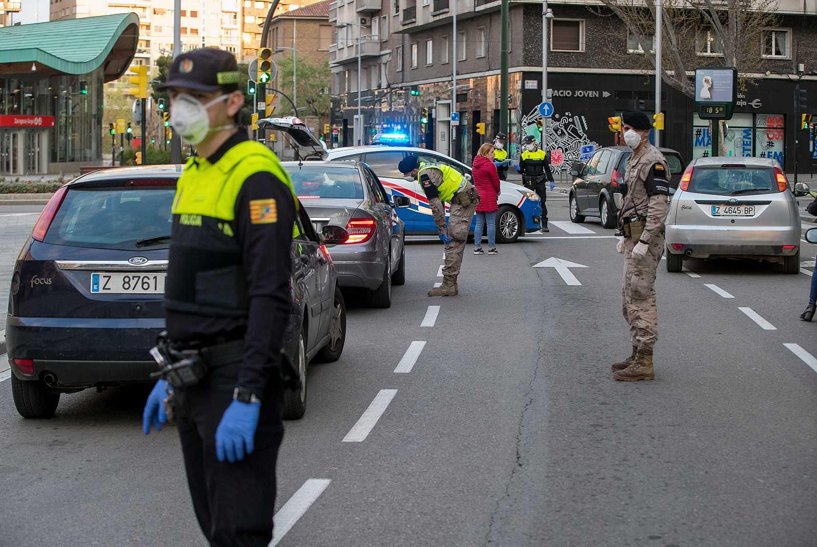 Agentes de la Policía Local ayudados por personal militar controlan la circulación de vehículos por una avenida zaragozana en una jornada marcada por las medidas del estado de alarma a causa del coronavirus.
