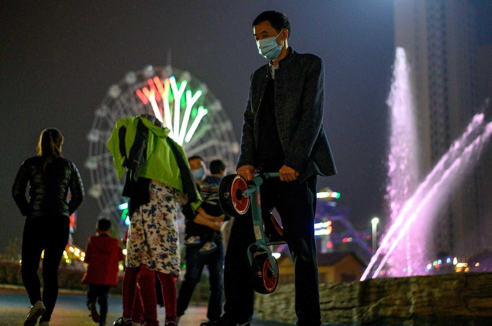 Personas con mascarillas en un parque temático de Macheng, Hubei