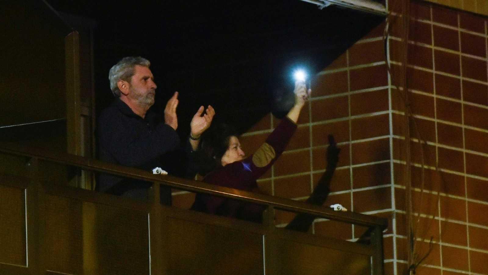 Vecinos del Hospital de Cruces, en Barakaldo (Bizkaia), aplauden y utilizan la linterna del móvil desde sus balcones