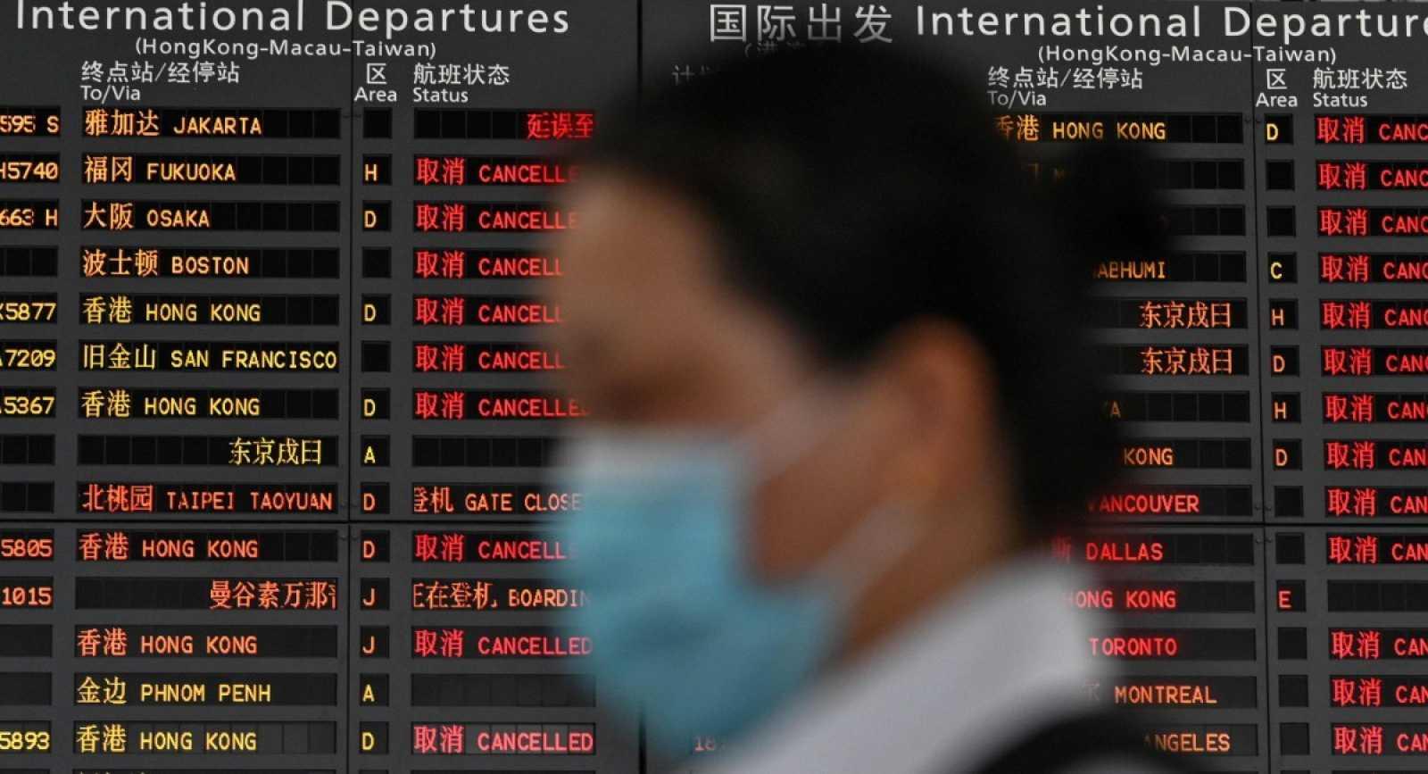 Una mujer con mascarilla espera en el aeropuerto de Shanghái