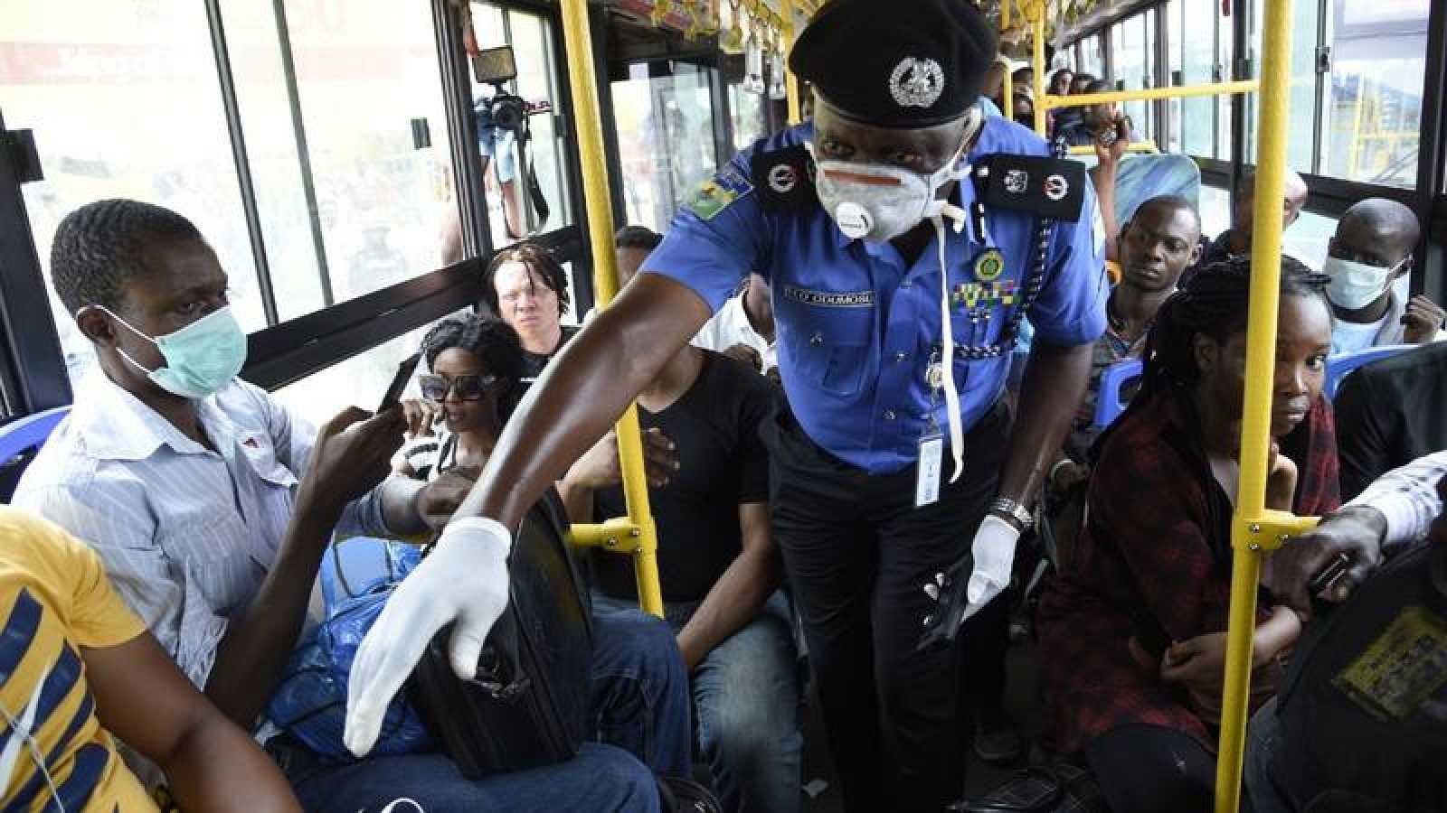 Policía nigeriano supervisando la distancia entre pasajeros por el coronavirus