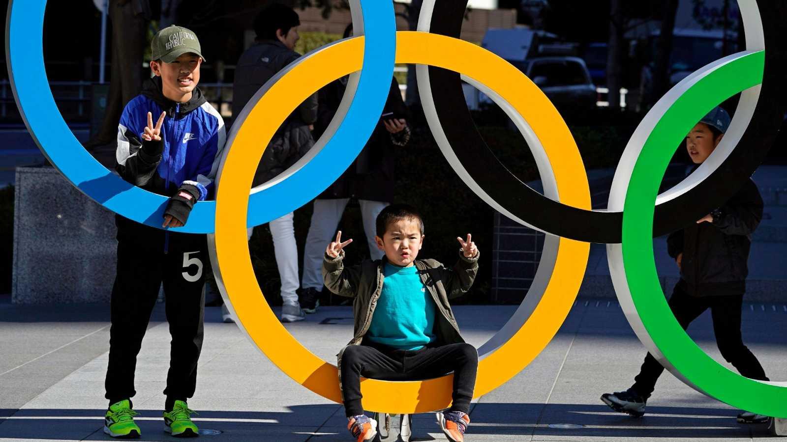 Un niño posa para una foto en uno de los aros olímpicos