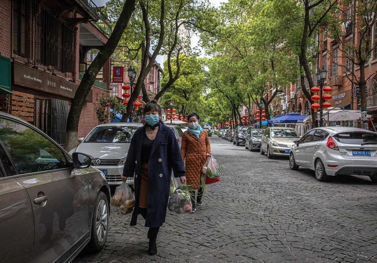 Dos mujeres llevan las bolsas de la compra en las calles de Wuhan
