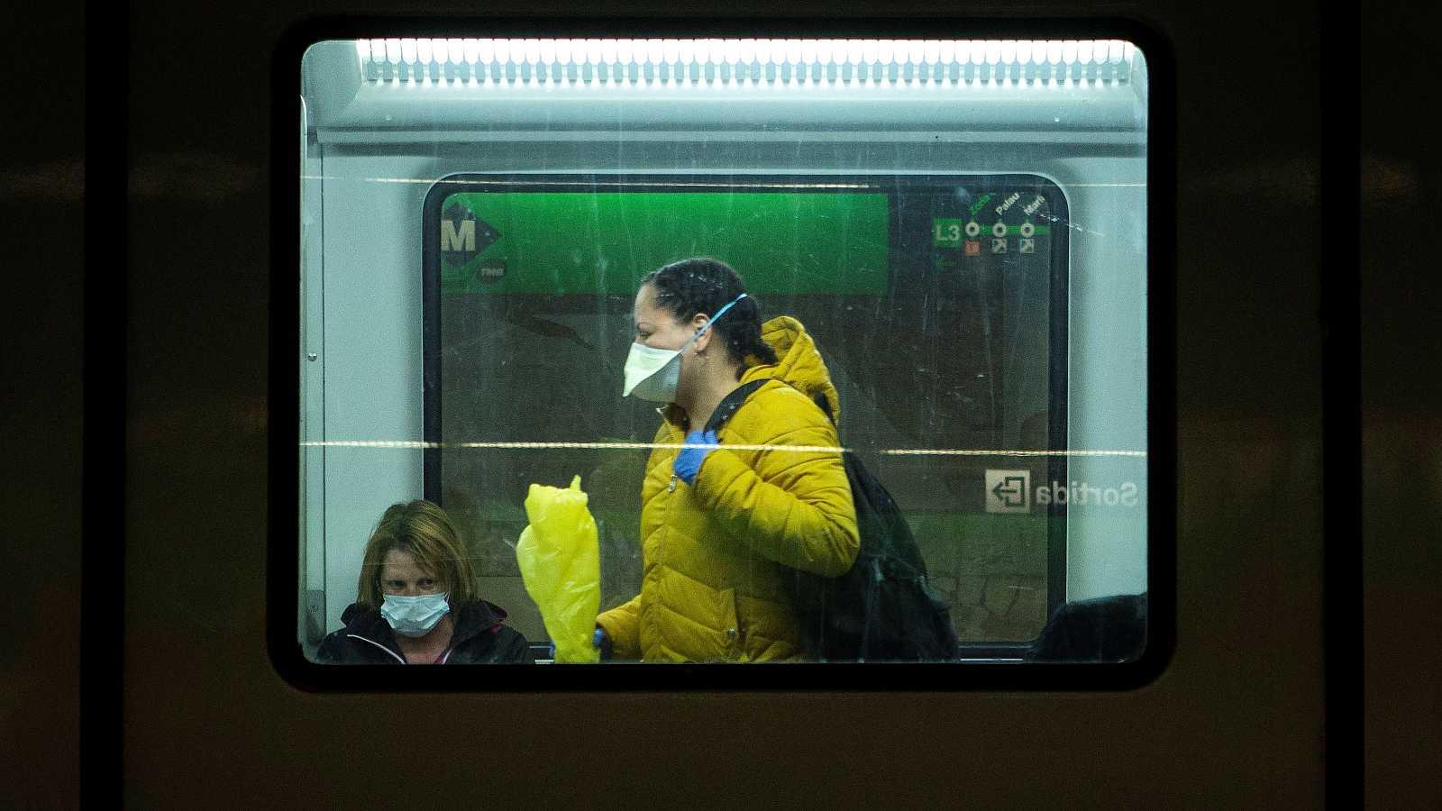Usuarias del metro de Barcelona, con mascarillas protectoras.