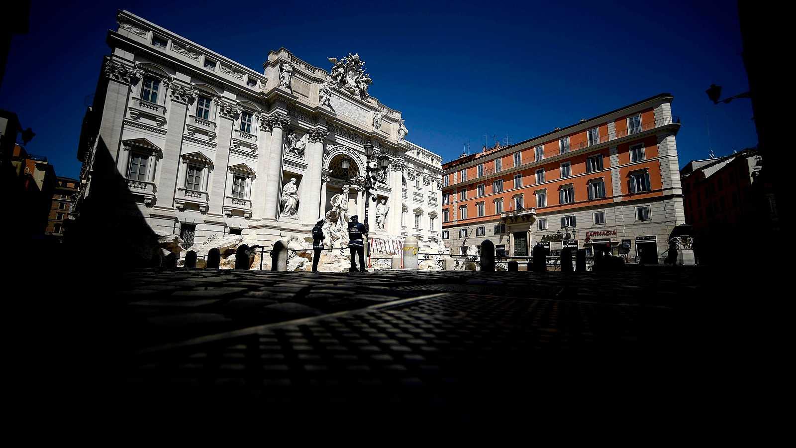 Coronavirus en Italia: Agentes de policía patrullan en una desierta Fontana de Trevi, en Roma.