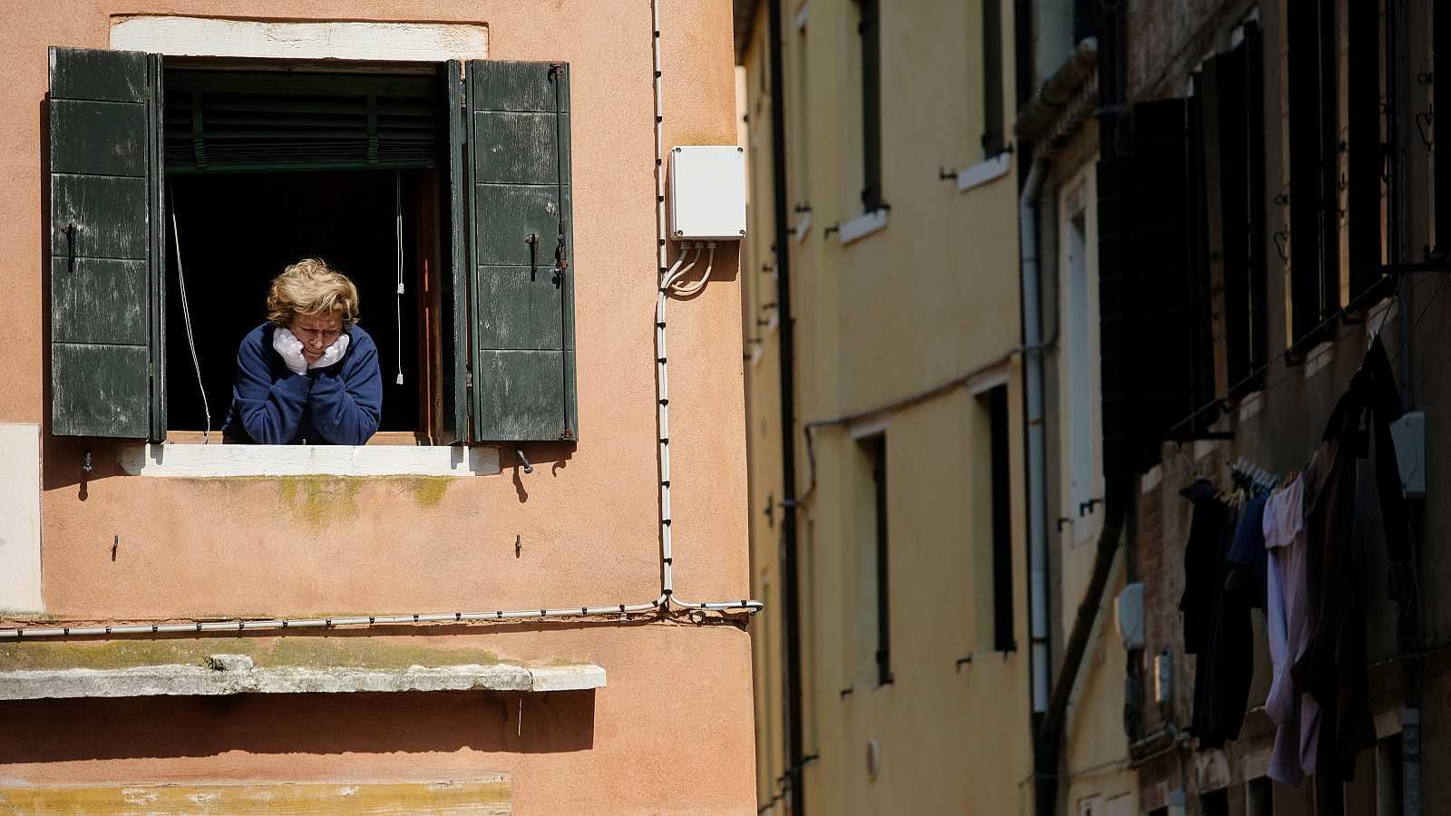 Coronavirus Italia: Una mujer asomada a la ventana de una vivienda en Venecia.