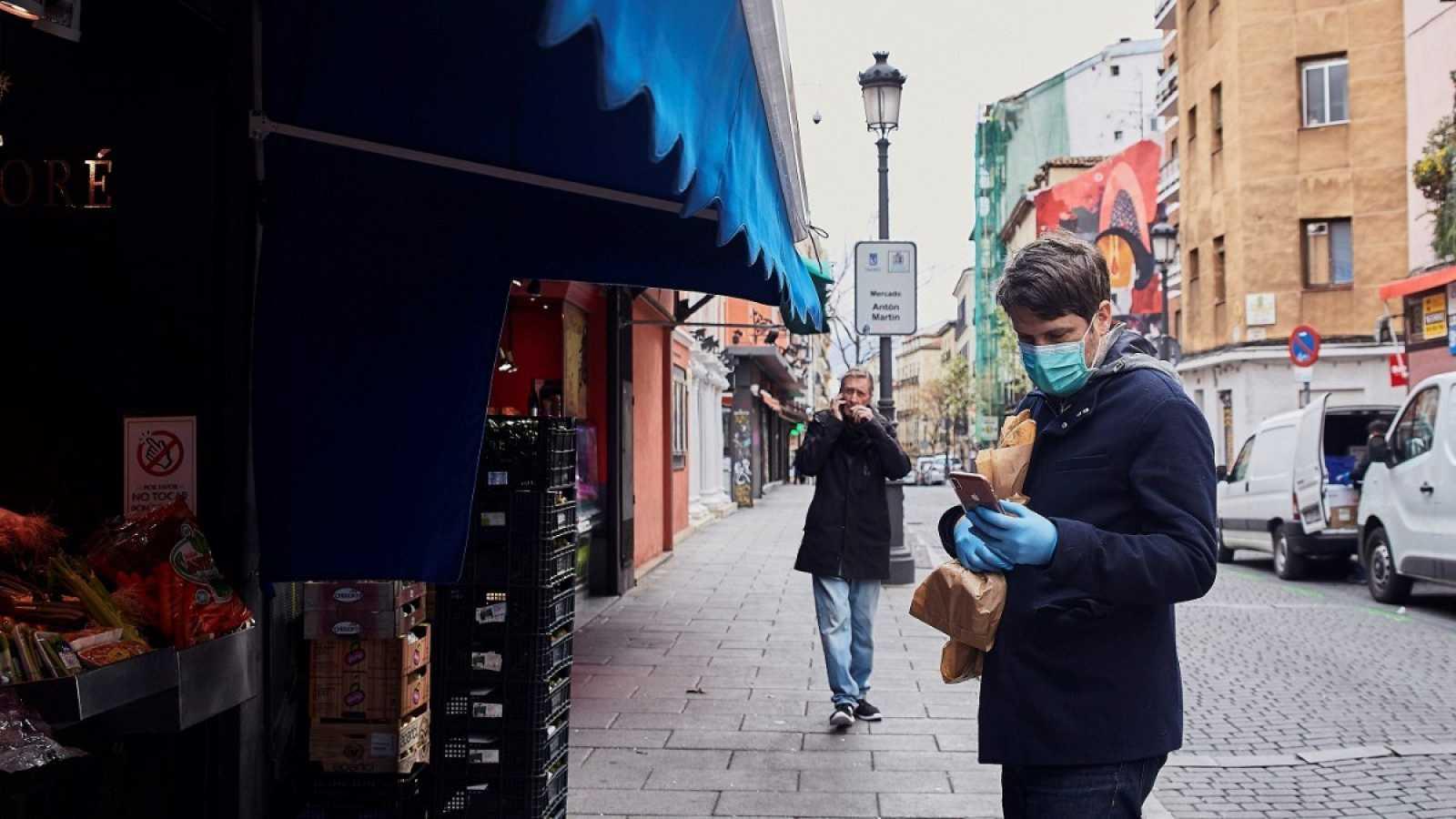 Un hombre espera su turno en una frutería en Madrid