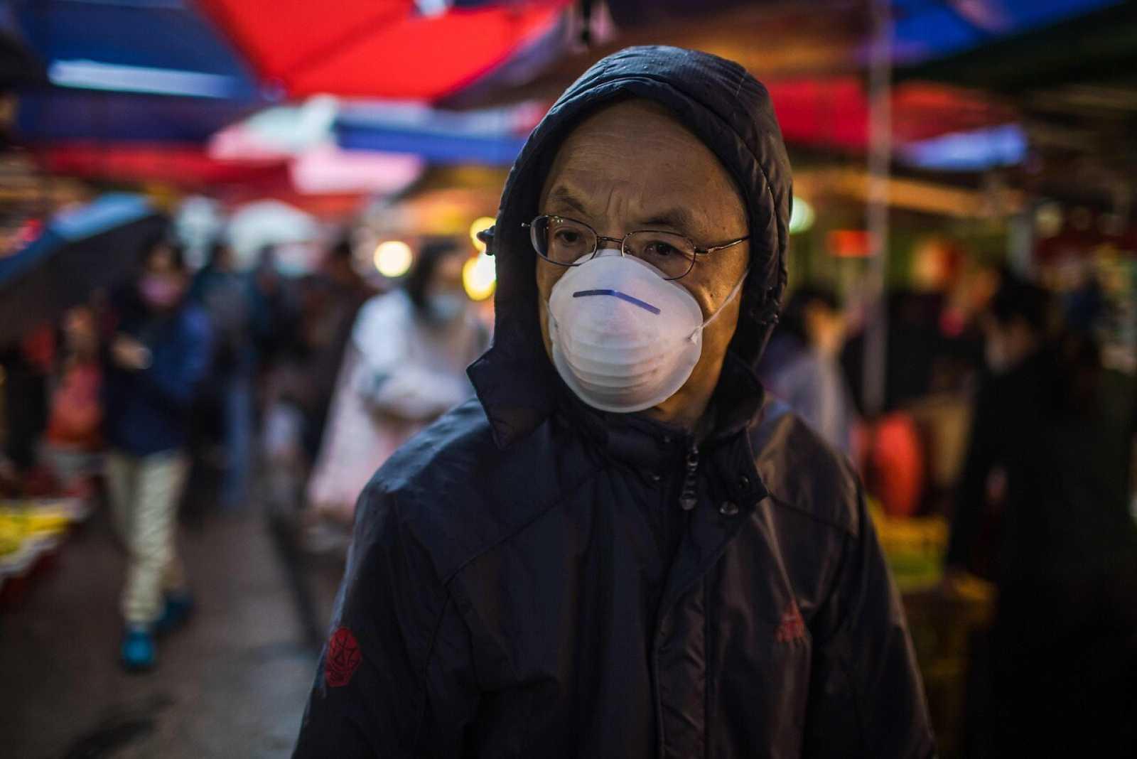 Un hombre pasea con mascarilla por un mercado de comida