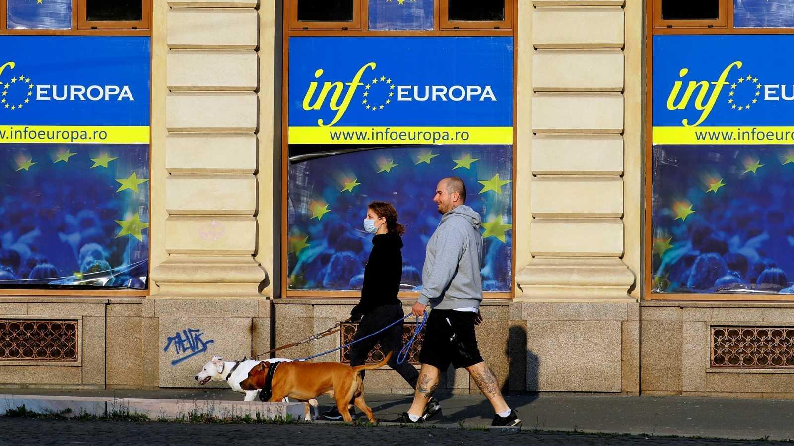 Una pareja pasea con sus perros delante del centro de información de la UE