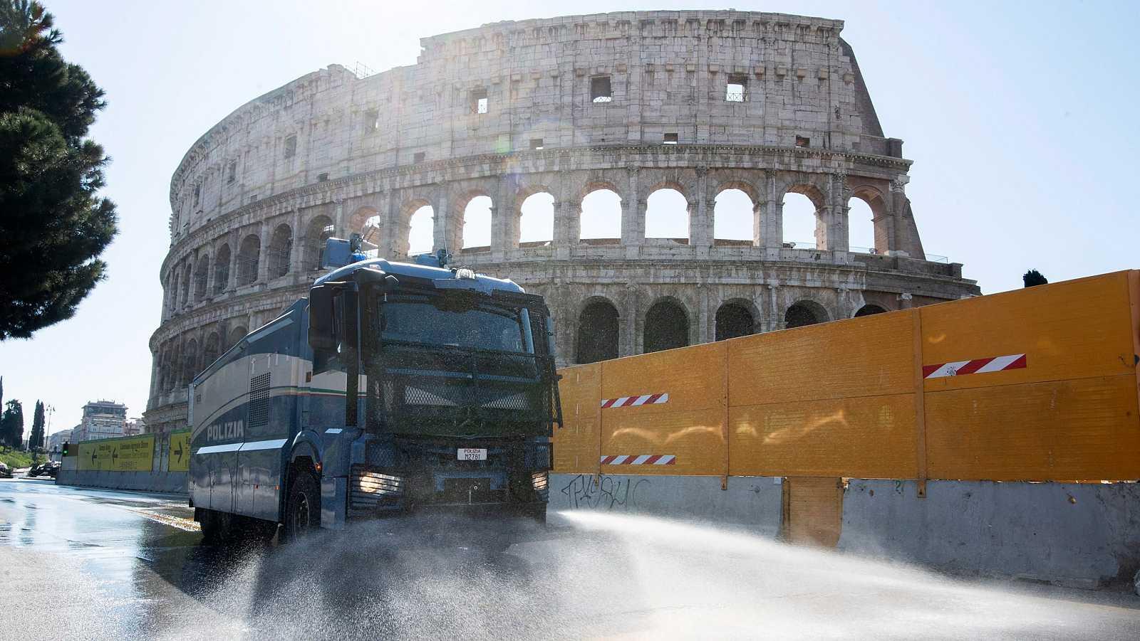 Coronavirus Italia: Un camión con un cañón de agua limpia las calles en Roma junto al Coliseo.