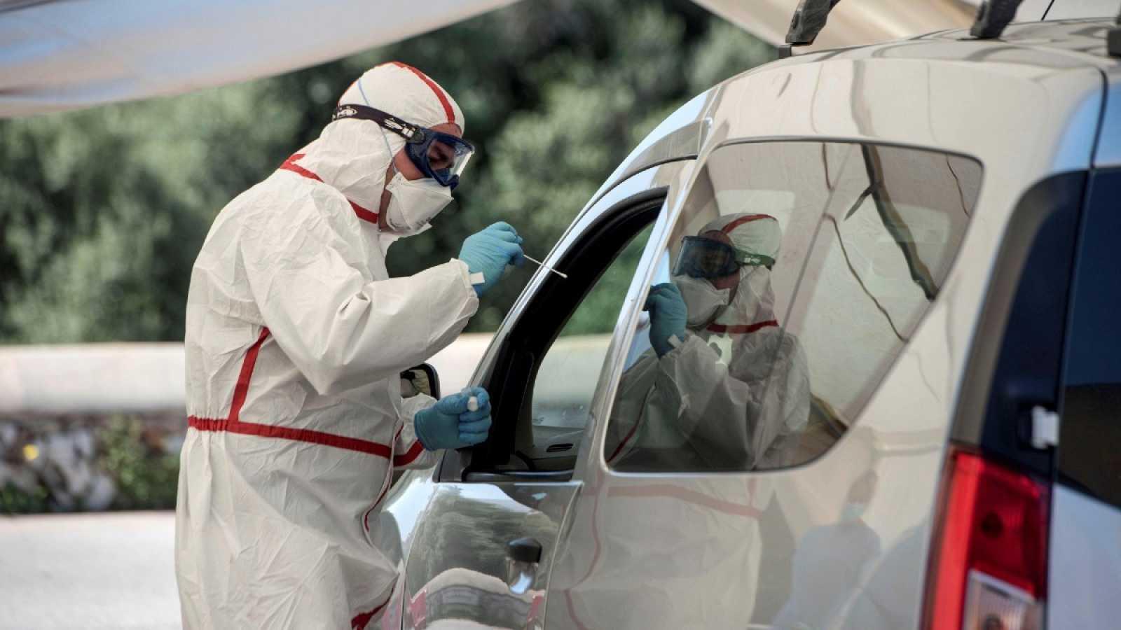 Un sanitario hace tests rápidos para detectar el coronavirus provisto de mascarilla y equipo de protección individual