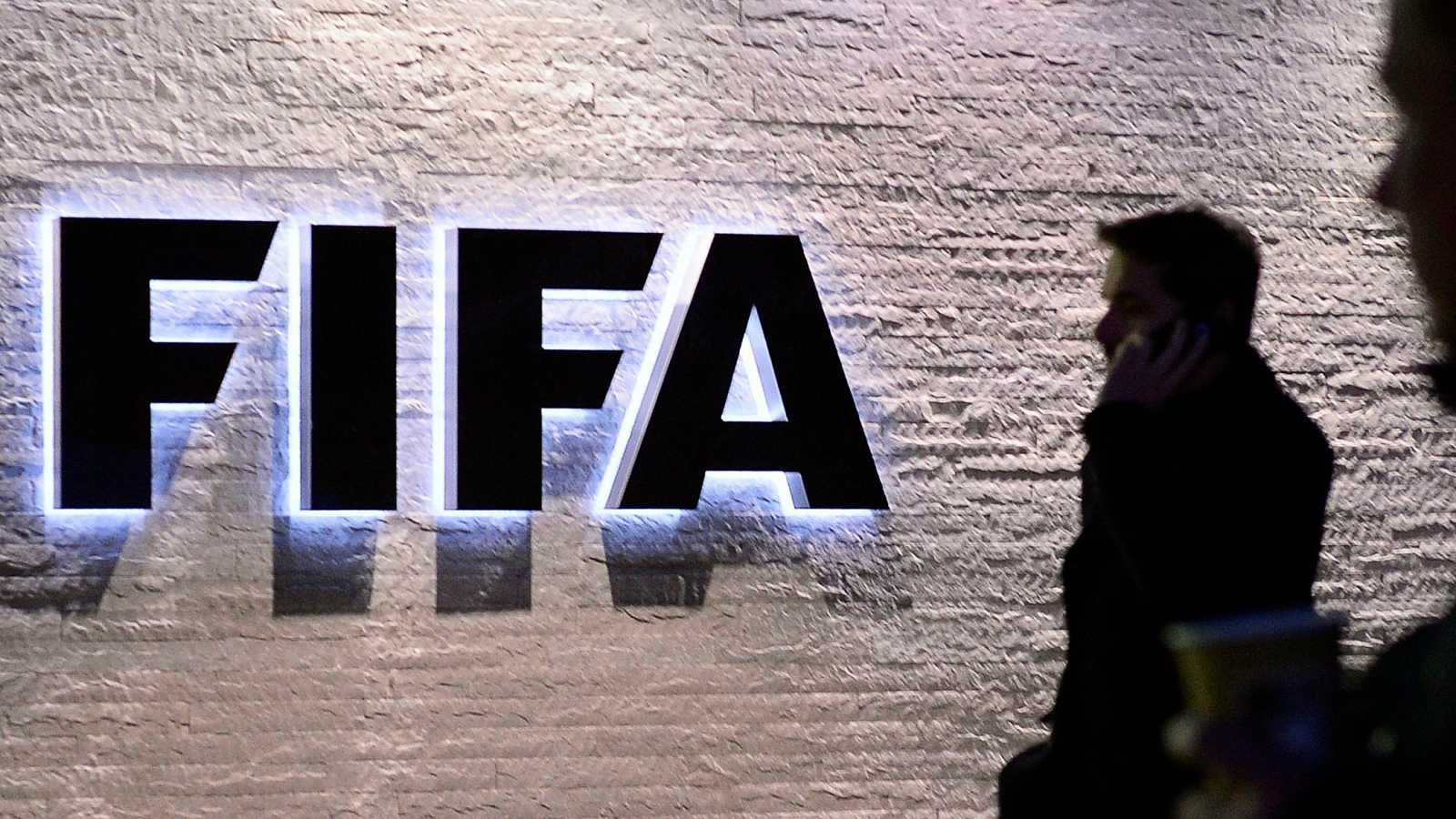 Varios periodistas permanecen a la entrada de la sede de la FIFA en Zúrich, Suiza