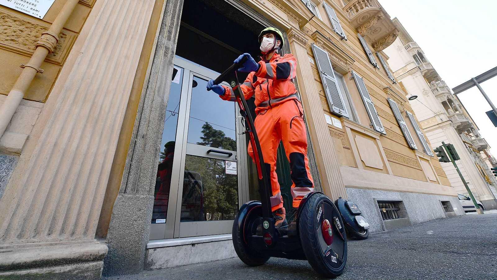 Voluntarios de Cruz Roja recorren las calles de Génova en vehículos segway ecológicos para repartir mascarillas y medicinas a domicilio