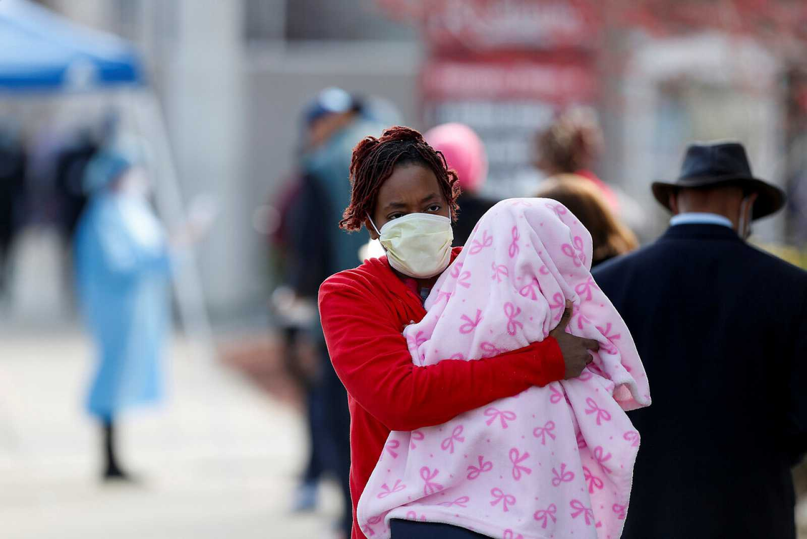 Una mujer con su hija en brazos espera para hacerse la prueba del coronavirus en Chicago
