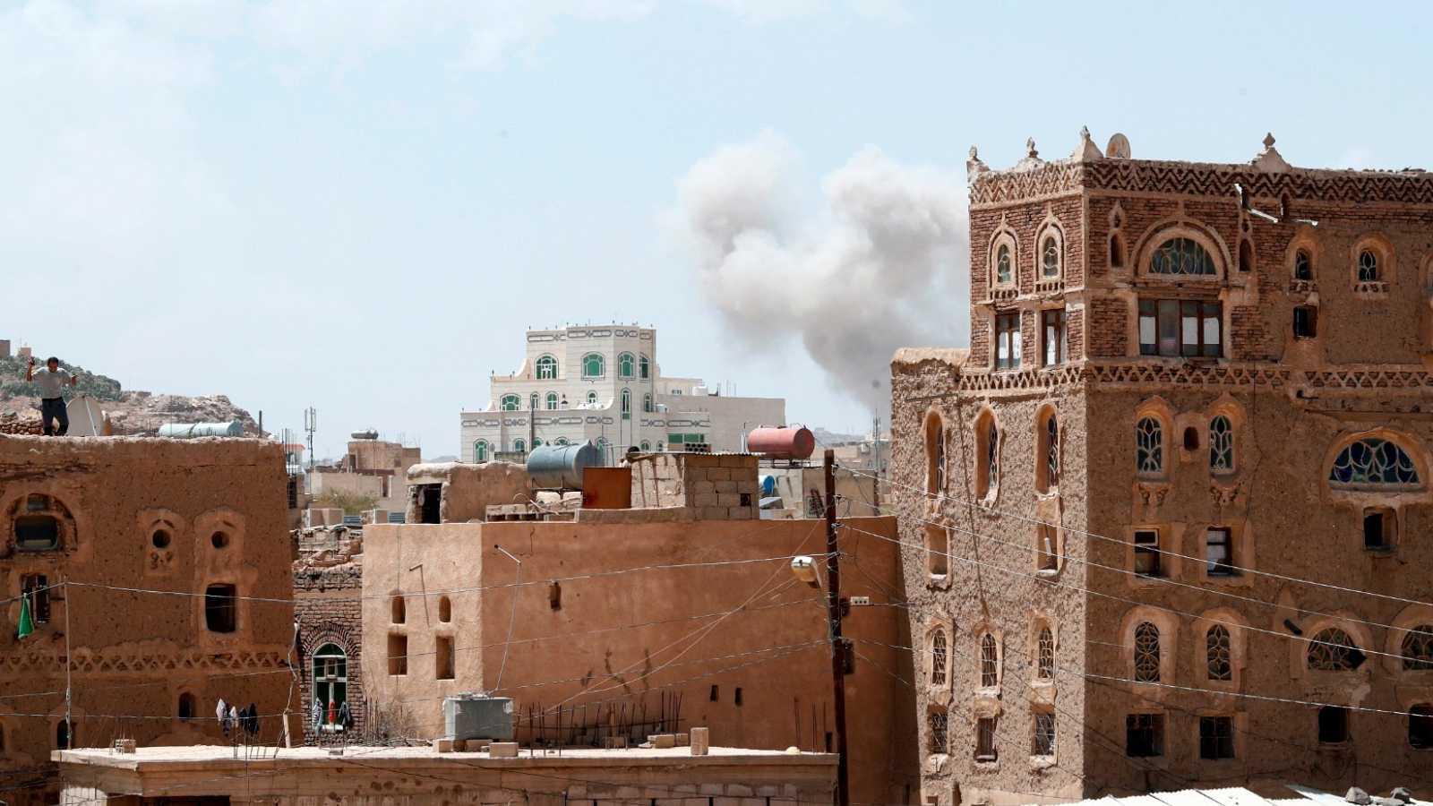 El humo asoma sobre las casas tras un ataque aéreo en Sanaa