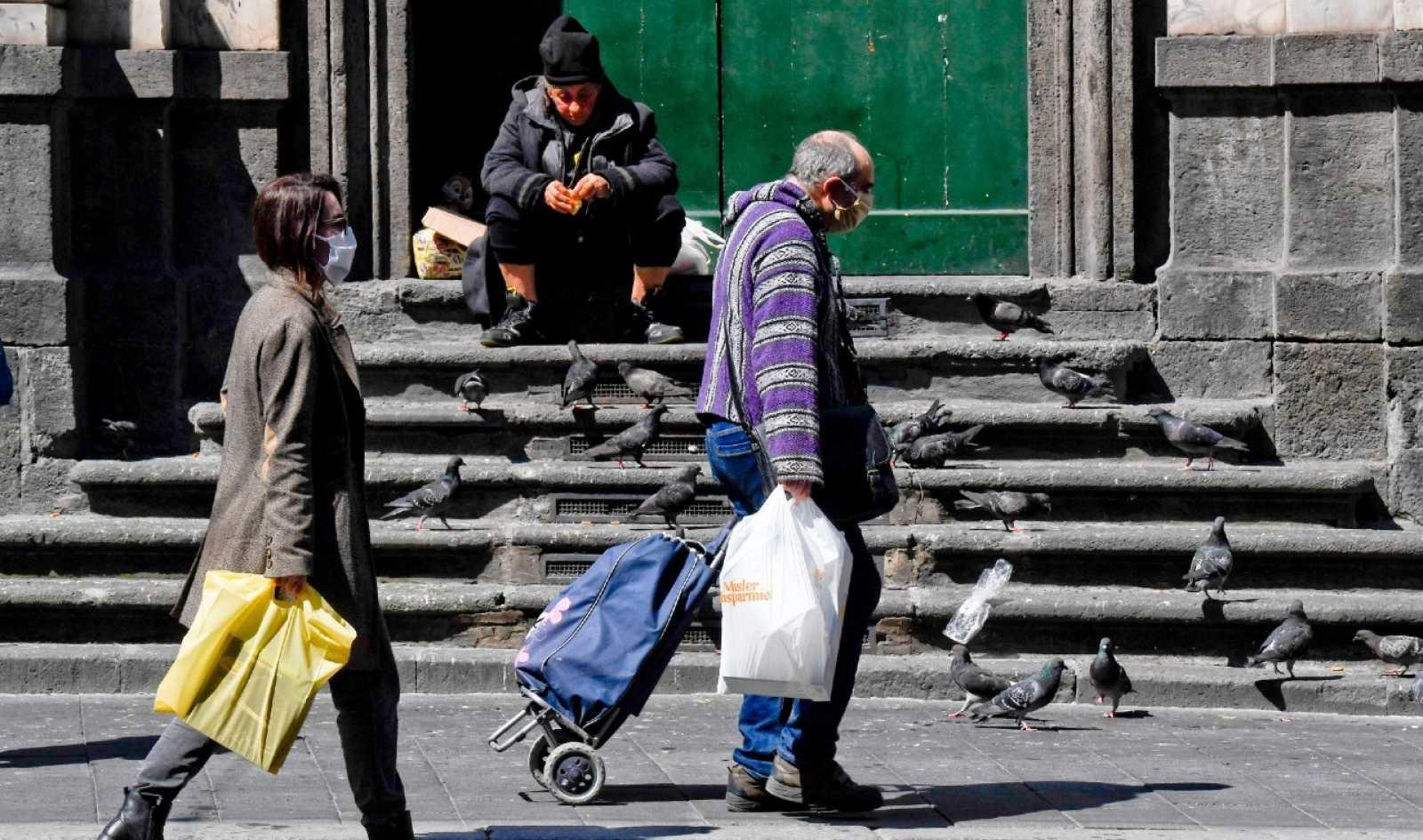 Una mujer sin hogar ni protección contra el coronavirus alimenta a las palomas en Nápoles