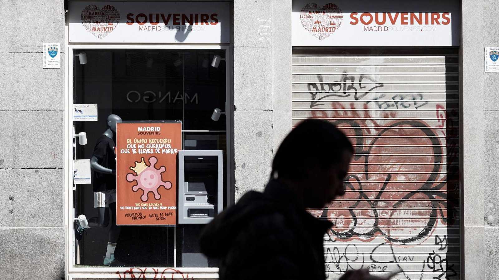 Una persona pasa delante de un establecimiento cerrado durante el estado de alarma en Madrid por la pandemia del coronavirus