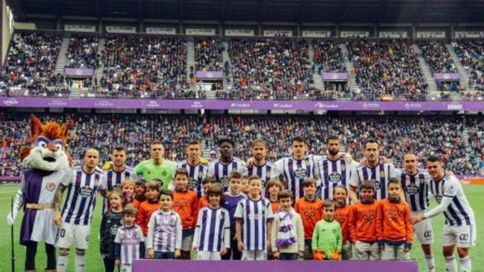 El equipo titual del Real Valladolid posa ante su público en el útlimo partido de Liga antes de la suspensión por el coronavirus.