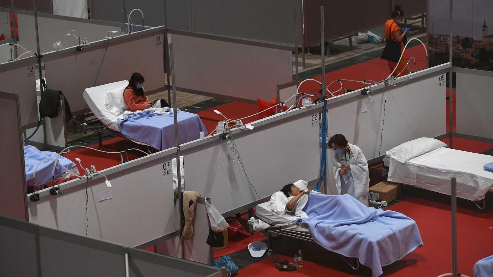 Un sanitario conversa con un paciente en el hospital habilitado en IFEMA