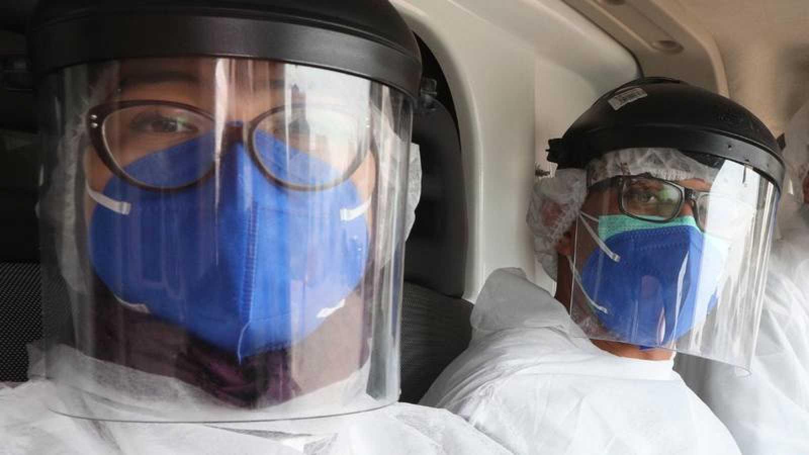 Dos trabajadores sanitarios tunecinos pertrechados con equipos de protección individual