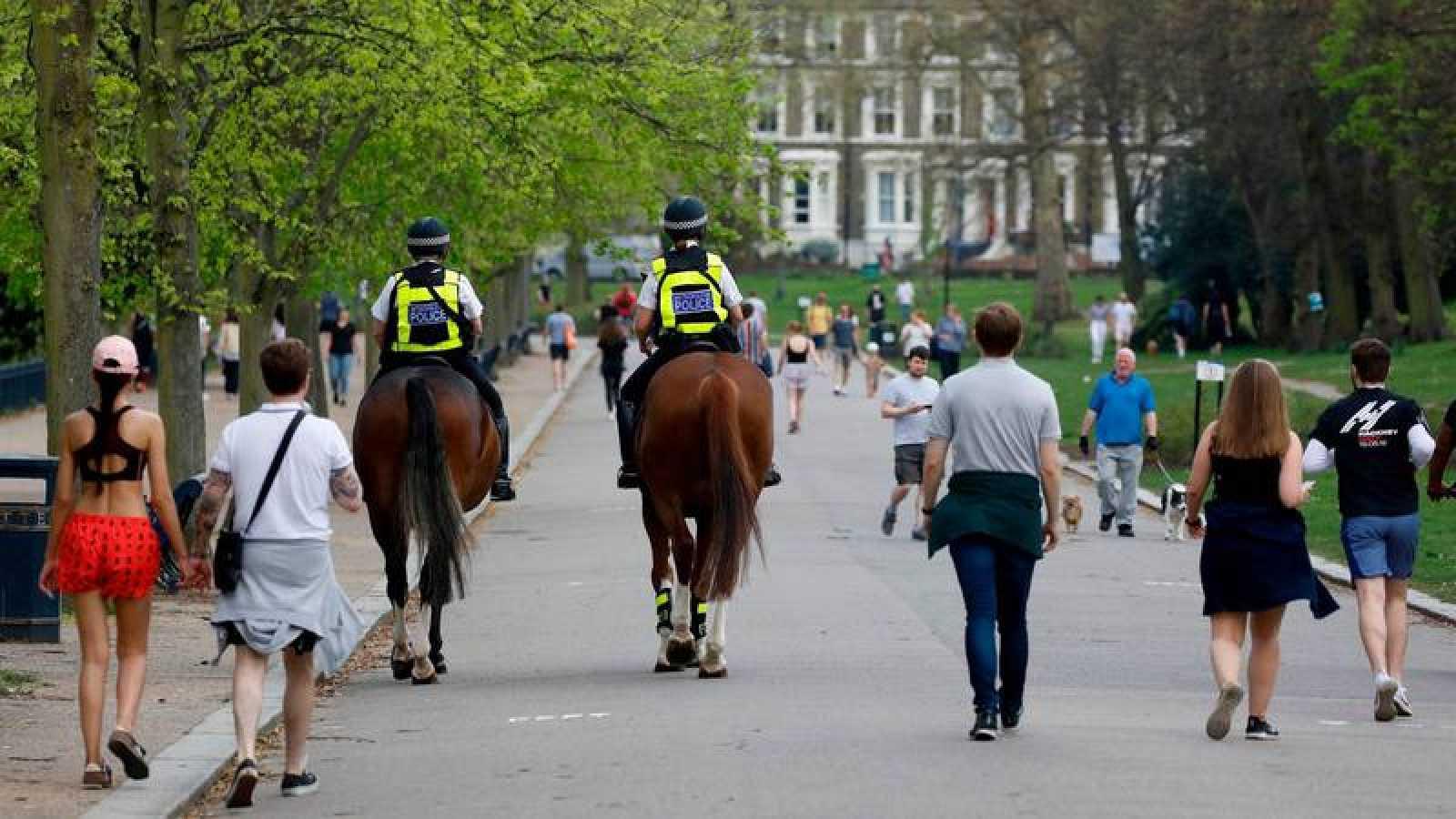Personas de paseo y patrulla de policías a caballo en un parque de londres, este sábado