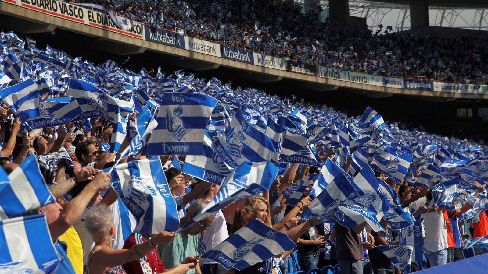 El público agita banderas blanquiazules en la grada del estadio de Anoeta.