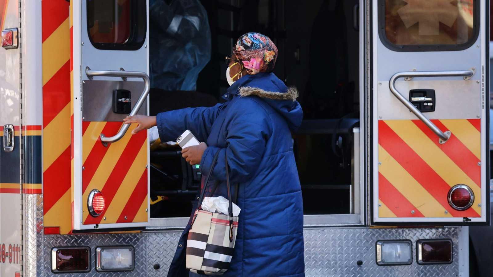 Una mujer acompaña a un paciente, trasladado en ambulancia en el barrio de Brooklyn, en Nueva York