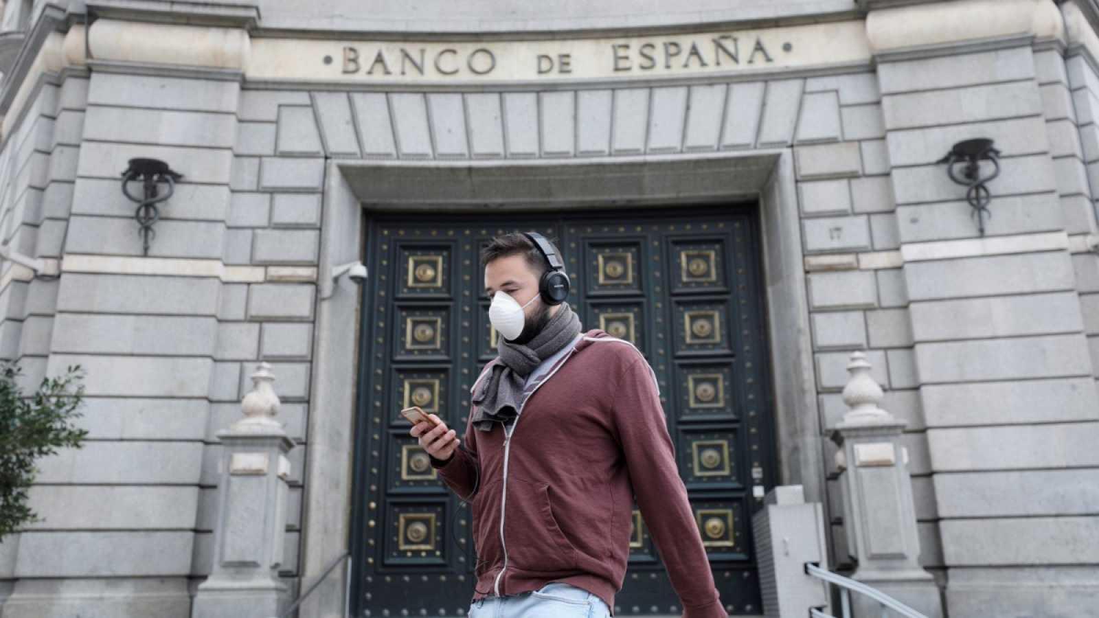 Un hombre camina con mascarilla frente al Banco de España en Madrid