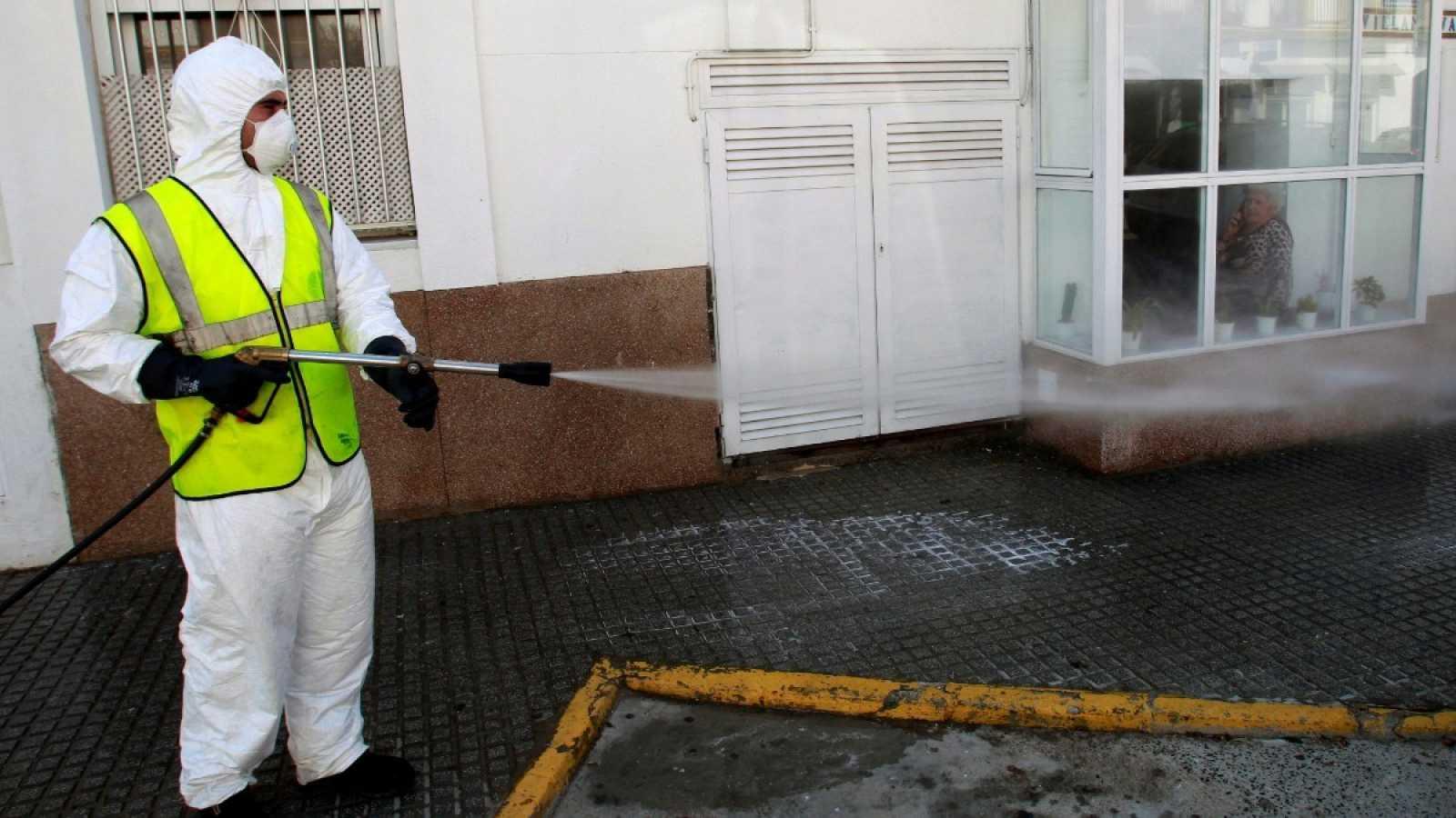 Una mujer habla por teléfono confinada en su casa, mientras observa a un operario desinfectando la calle