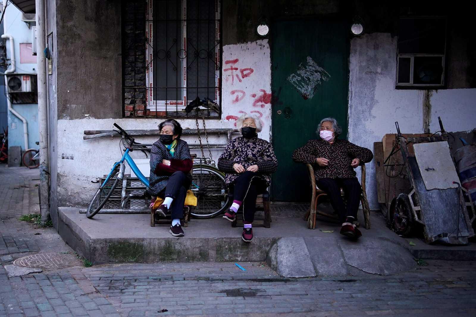 Residentes con máscaras en una zona residencial bloqueada en Wuhan