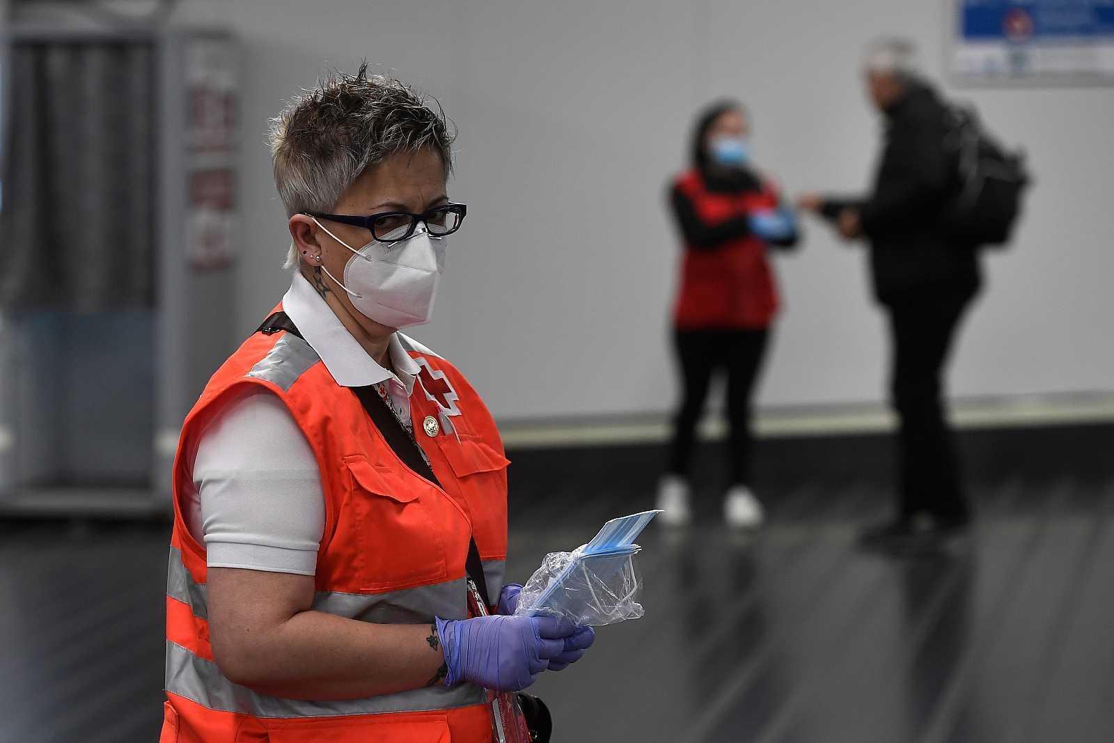 Un voluntario de la Cruz Roja distribuye mascaras faciales en la estación de Chamartín de Madrid.