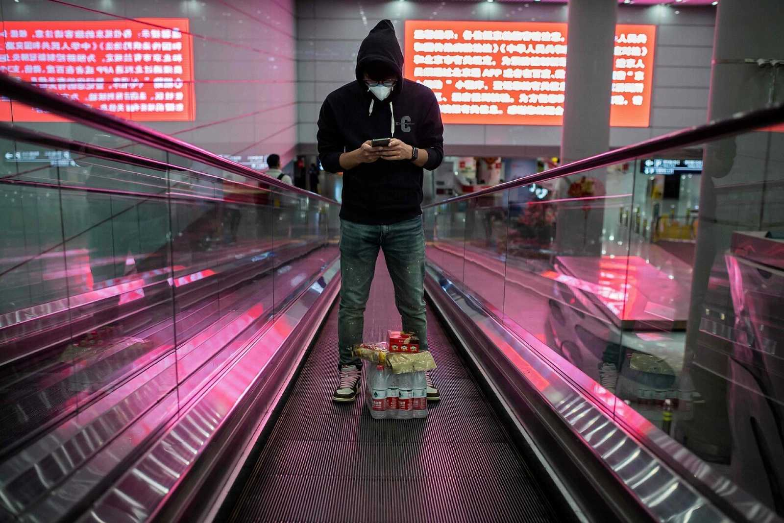 Un joven con mascarilla en el aeropuerto internacional de Pekín