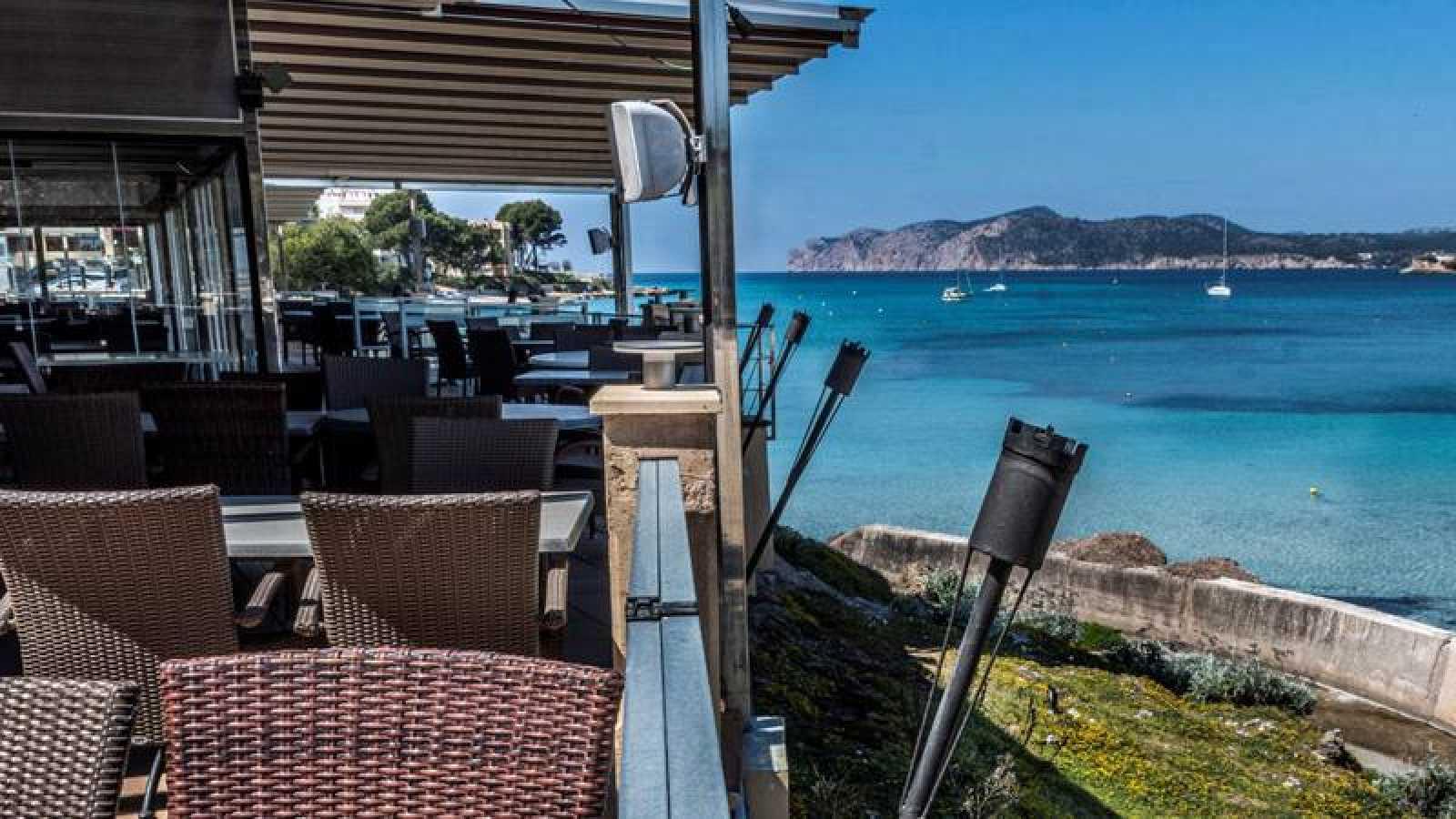 Terraza de un restaurante cerrado con vistas a una playa de Baleares.