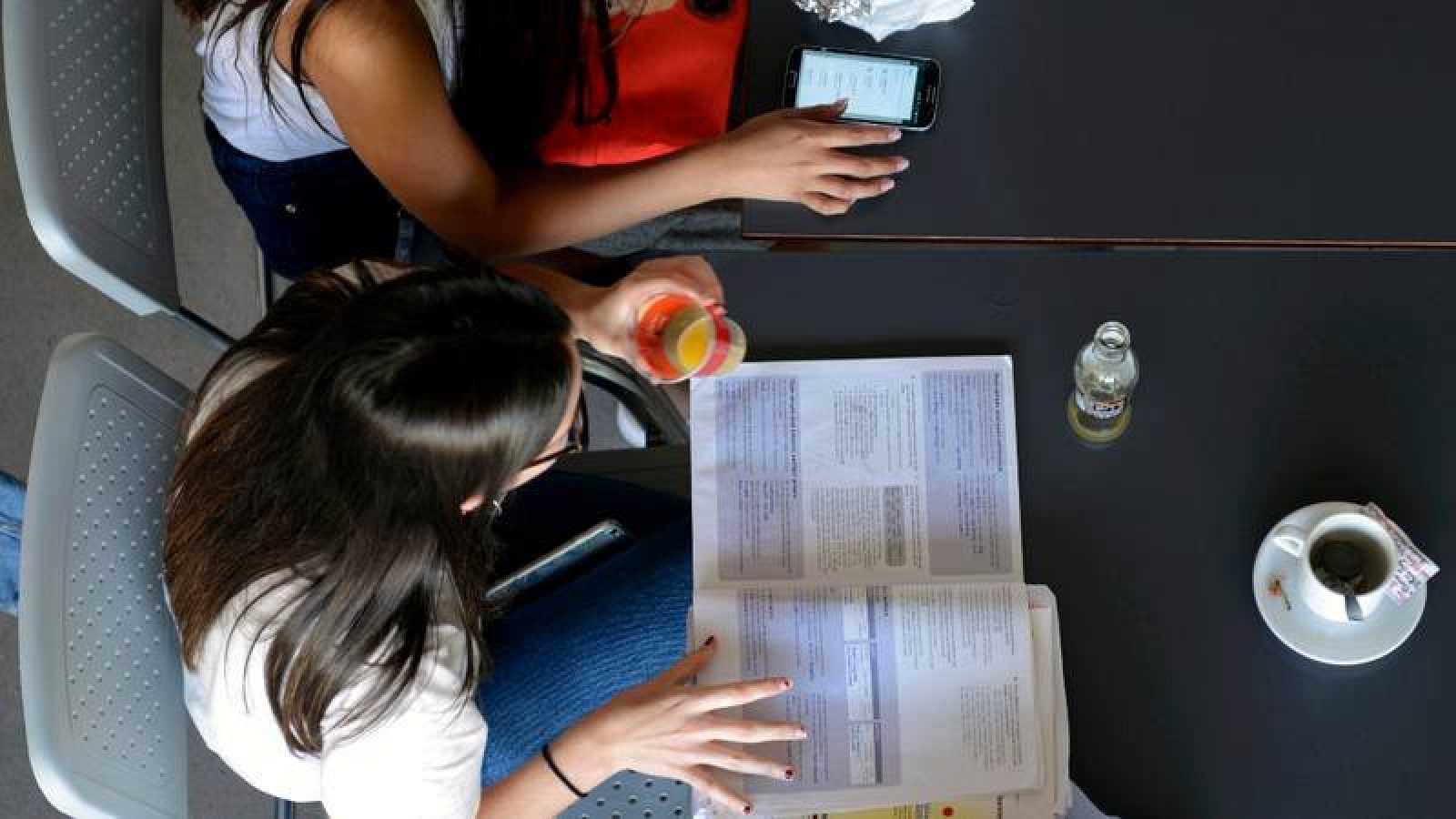 Dos estudiantes preparan un examen en la cafetería de la facultad