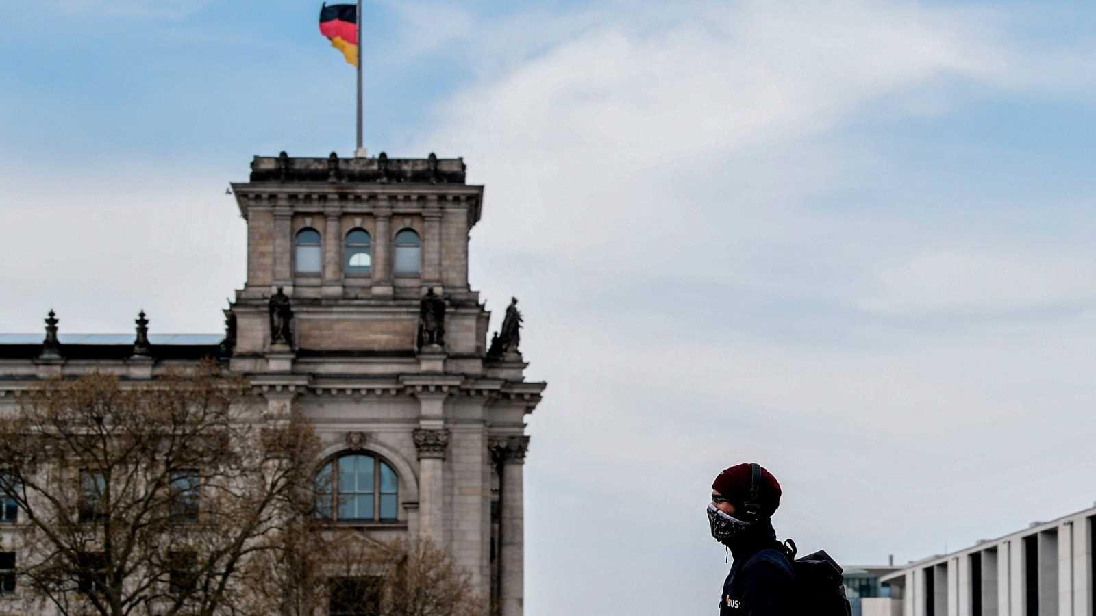 Un hombre con una máscara protectora camina enfrente del Bundestag, el parlamento alemán
