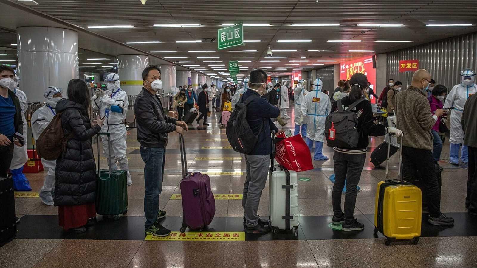 Pasajeros procedentes de Wuhan forman filas en la estación de tren de Pekín