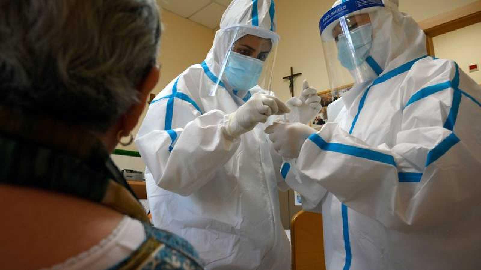 Profesionales sanitarios con trajes protectores toman una muestra para una prueba de Covid-19 en el Hospital Sant Miquel de Barcelona.