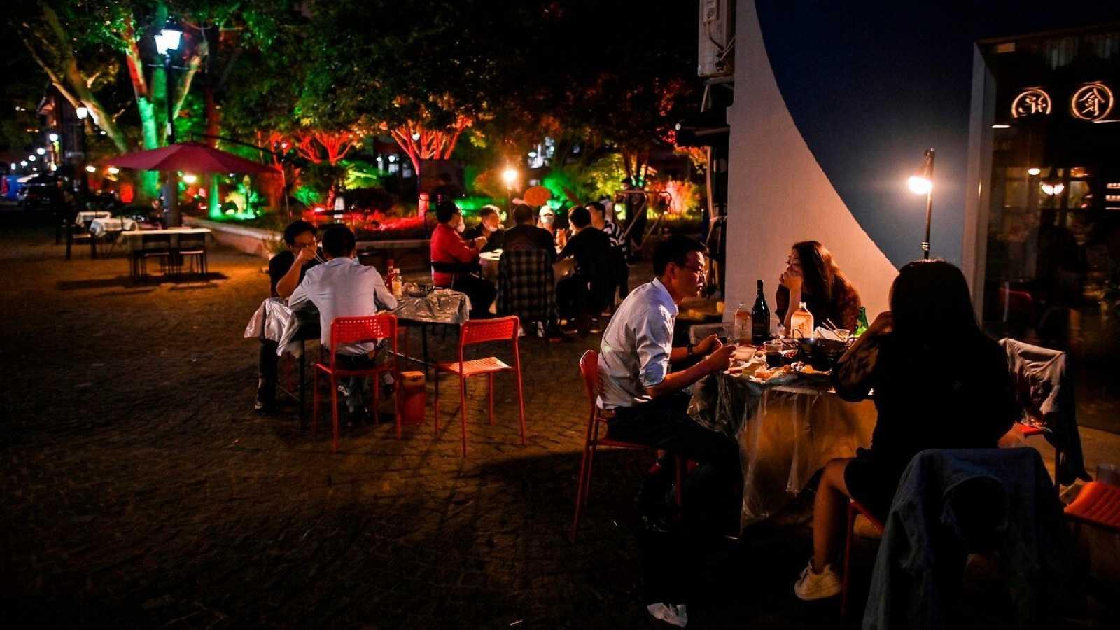 Varios clientes cenan en una terraza de un restaurante de Wuhan