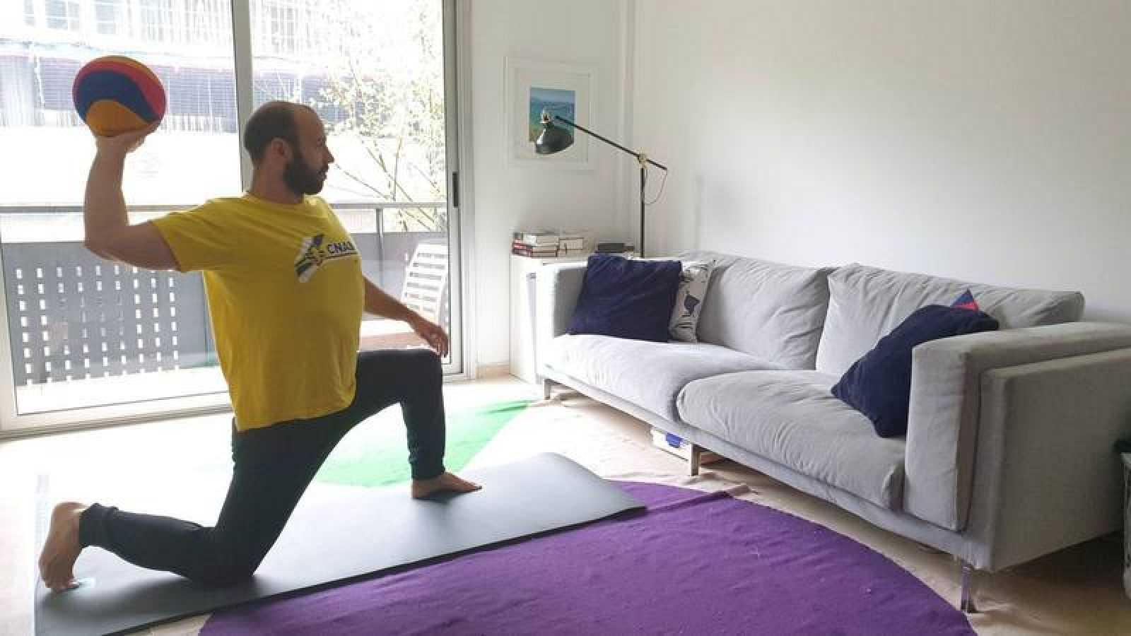Felipe Perrone se ejercita lanzando el balón al sofá en su casa