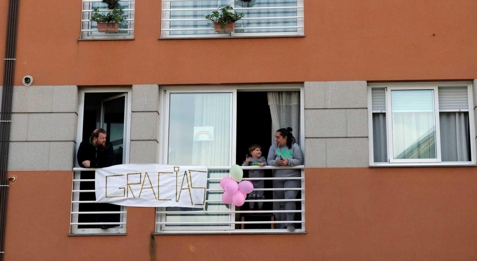 """Un niño se asoma a la ventana en Narón (A Coruña) para ver un desfile organizado por Bomberos y Policía Local para dar """"un aplauso para los niños y niñas"""" del pueblo."""