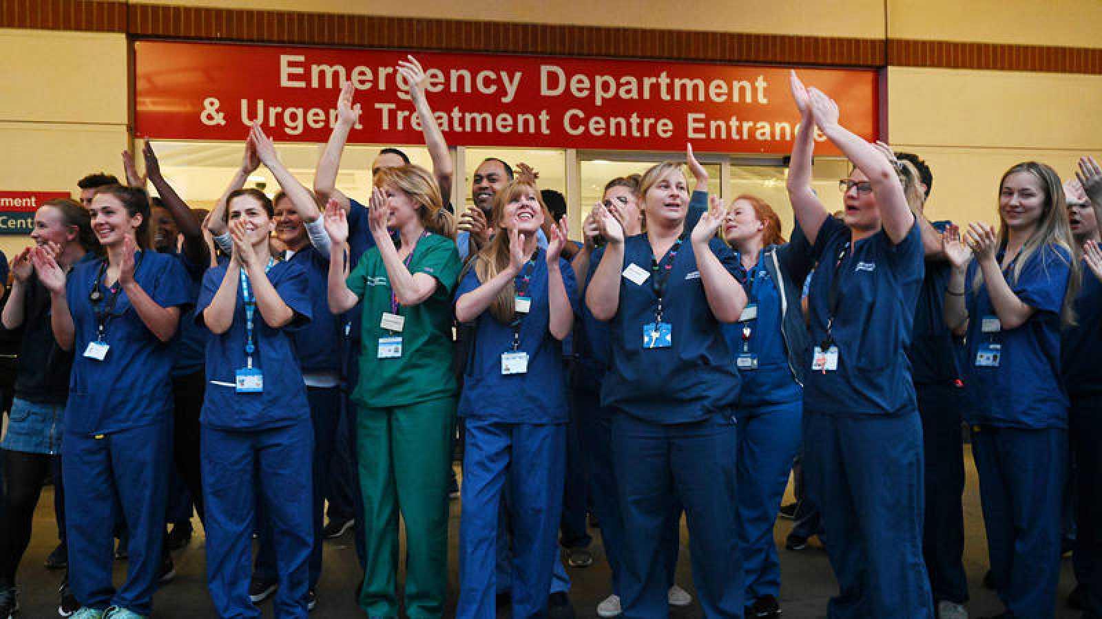 Personal sanitario de un hospital del Reino Unido se suma al aplauso a los profesionales del país.