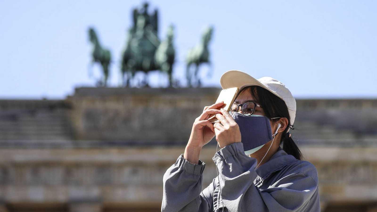 Una turista con mascarilla junto a la puerta de Brandenburgo en Berlín, Alemania