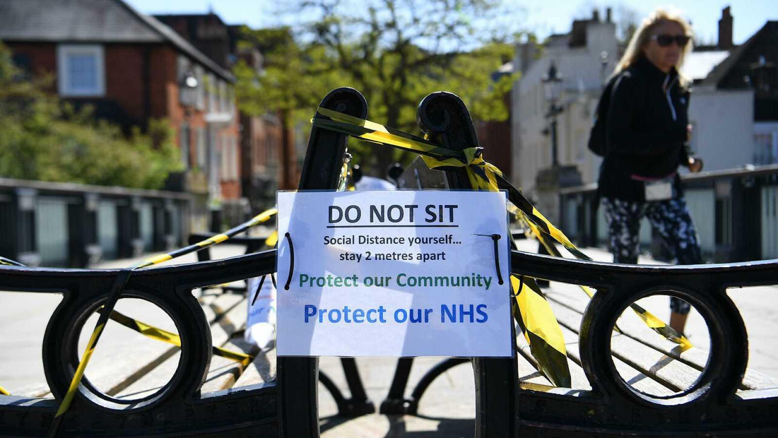Bancos fuera de los límites en Windsor, en Inglaterra, donde un cartel recuerda la norma de distancia social para contener el virus.