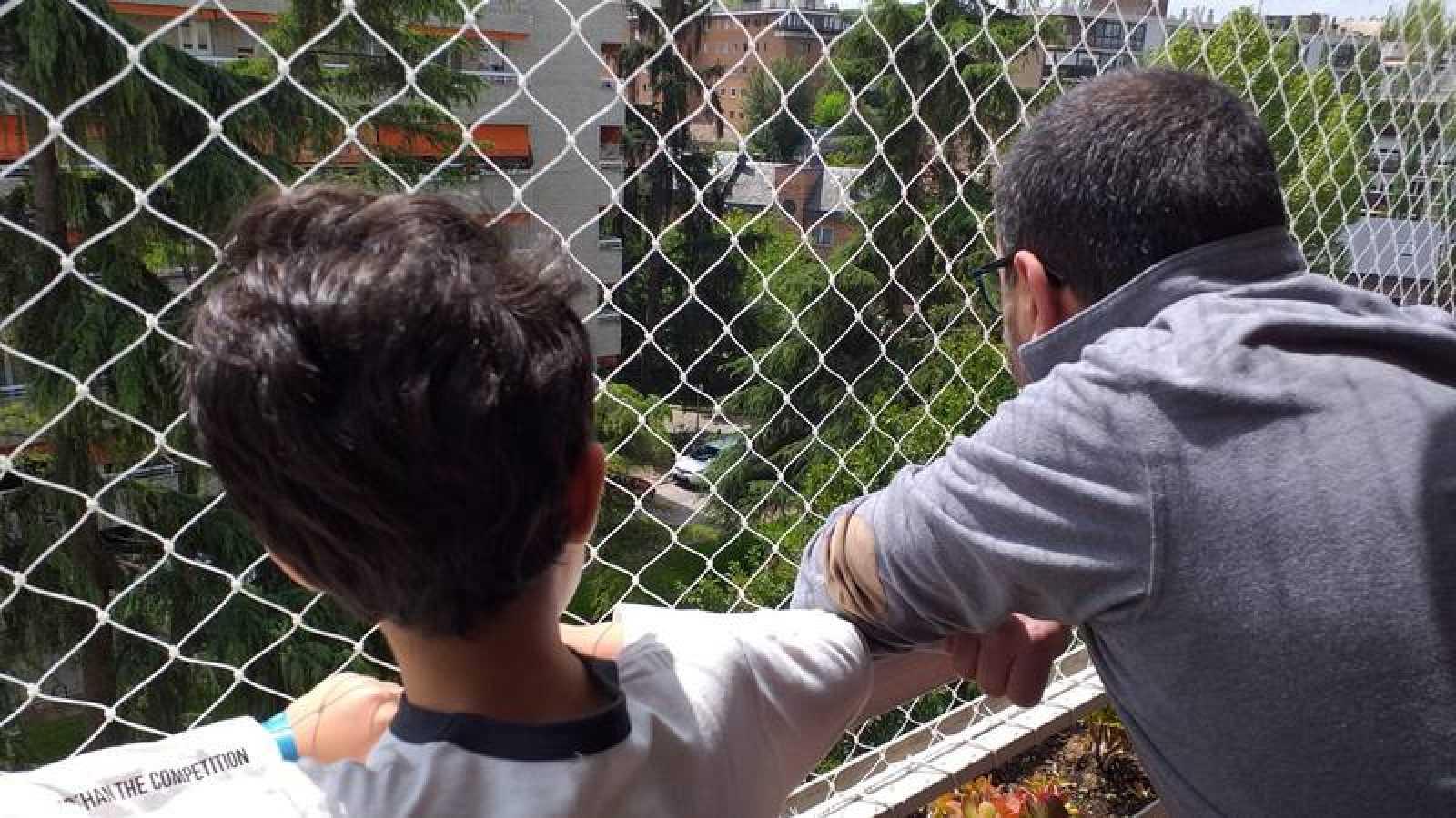 Nicolás, de 7 años, mira junto a su padre la calle pensando ya en las cosas que podrá hacer cuando salga.