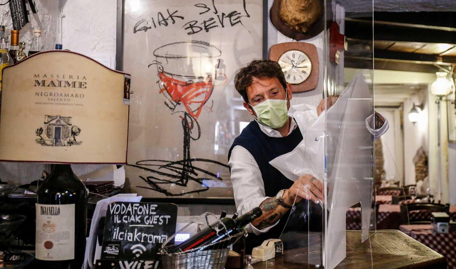 Un camarero prepara unas mamparas contra el coronavirus en un restaurante de Roma