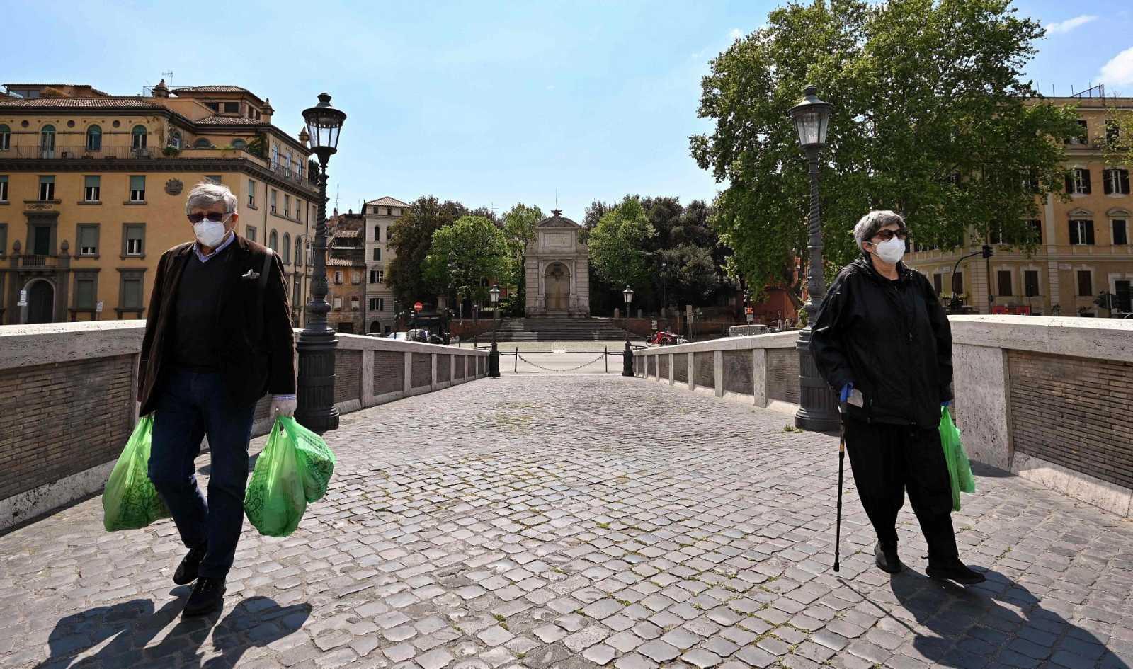 Dos italianos vuelven de hacer la compra este viernes en Roma