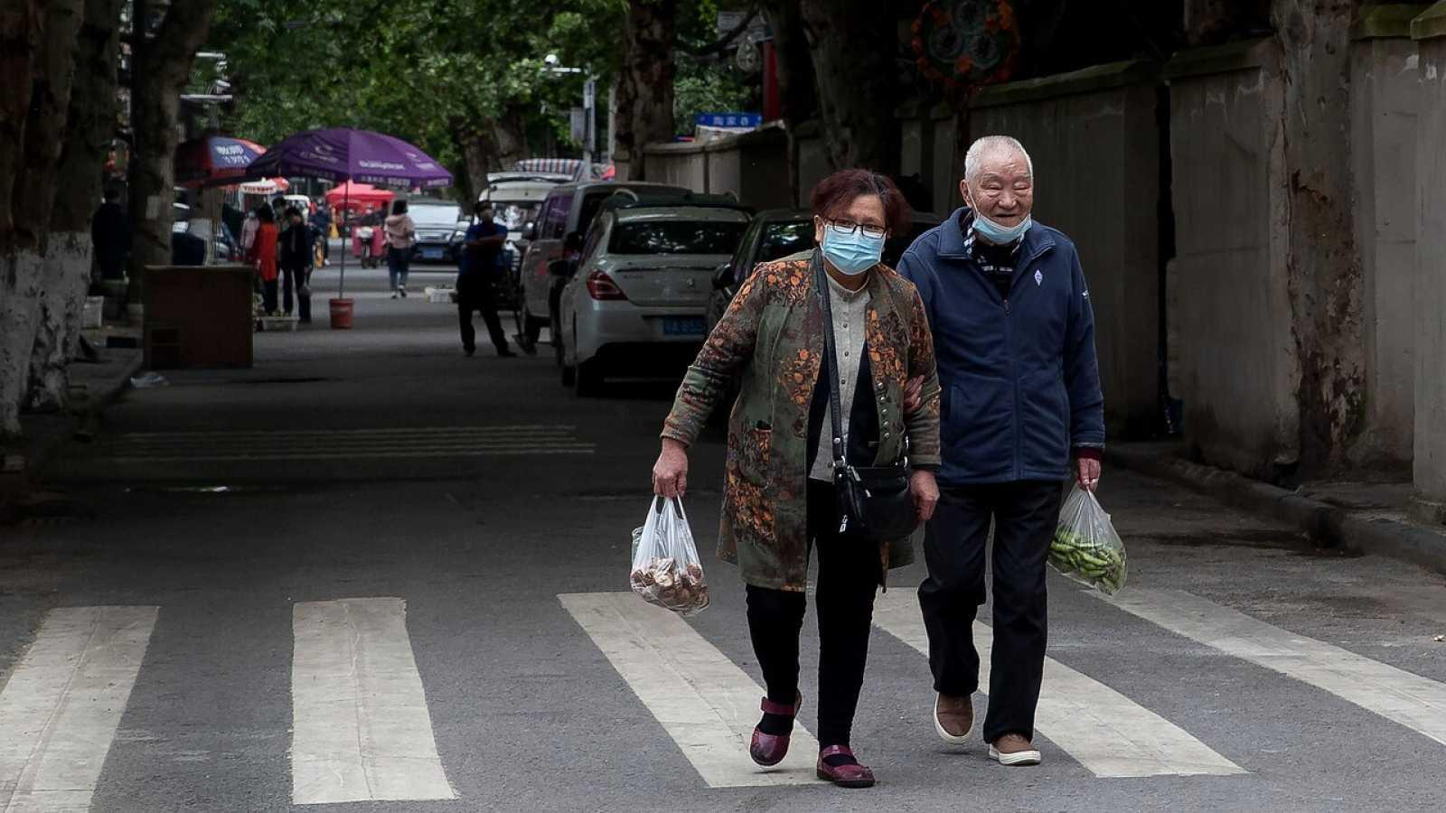 Dos personas cargan con las compras en Wuhan, China