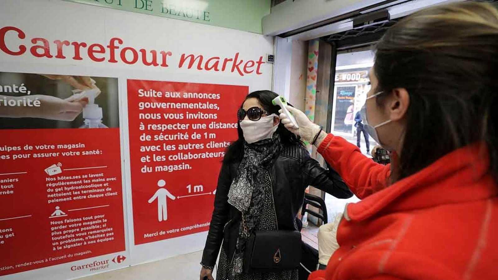Personal de Carrefour toma la temperatura a una clienta en una de sus tiendas francófonas.