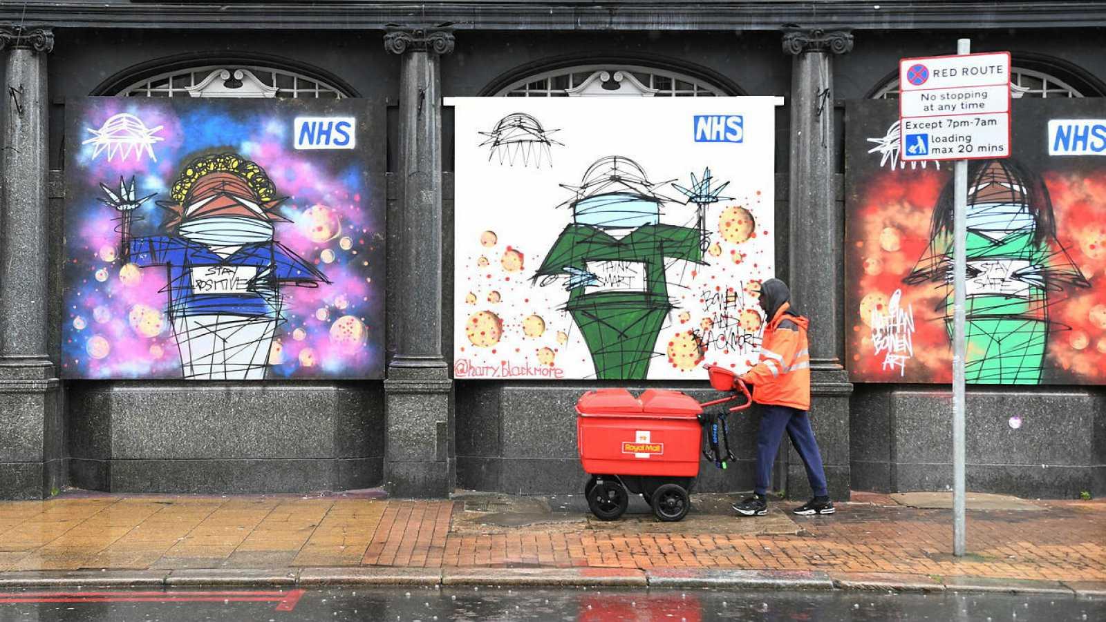 Un trabajador de Royal Mail pasa las obras de arte en apoyo del NHS (Servicio Nacional de Salud) en Londres, Reino Unido.